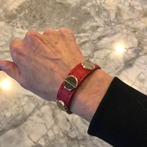 Red leather bracelet with gold tone screw motif